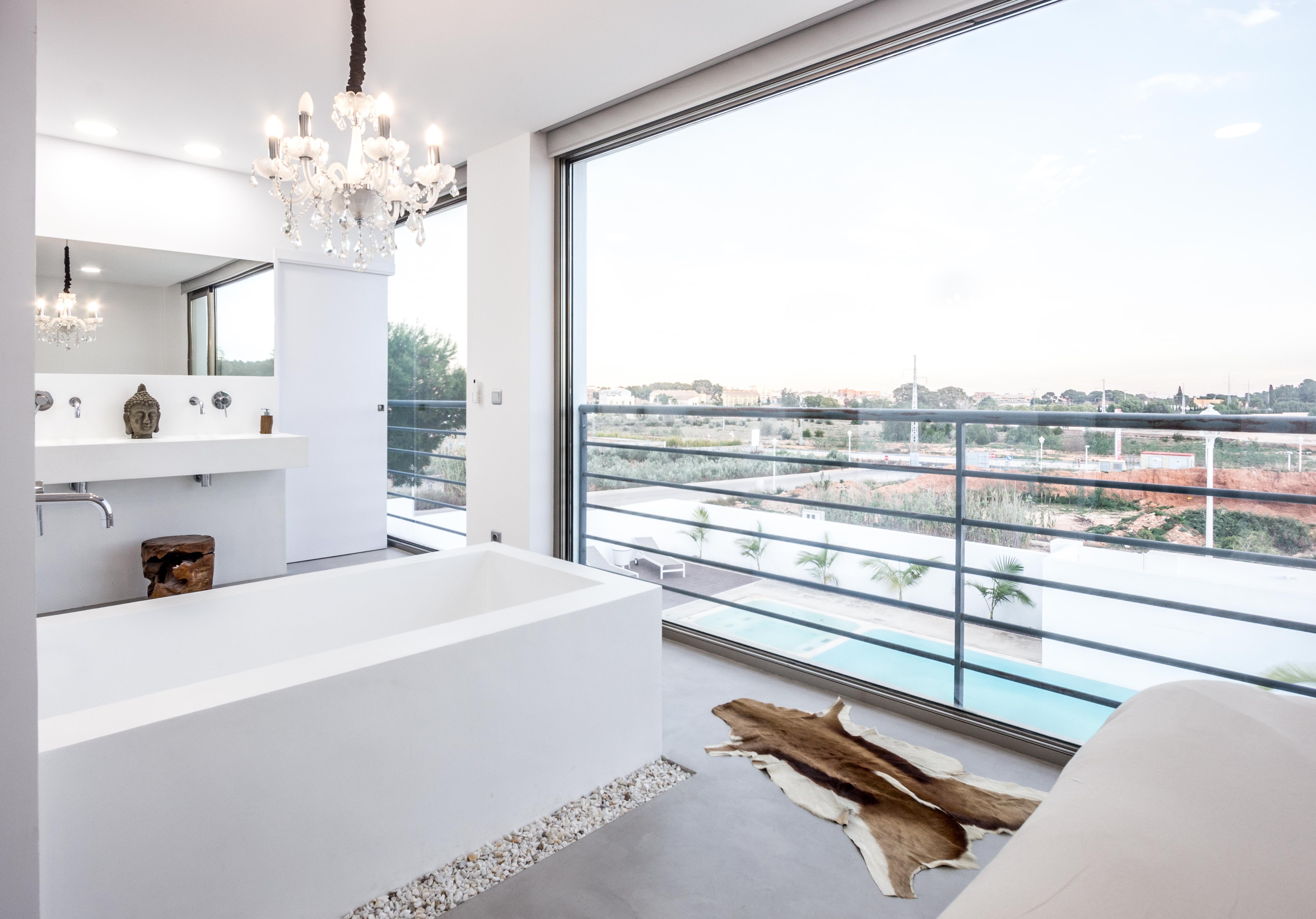 Bañera exenta en dormitorio y lavabo de microcemento blanco en casa cubo mediterranea. Chiralt arquitectos Valencia.