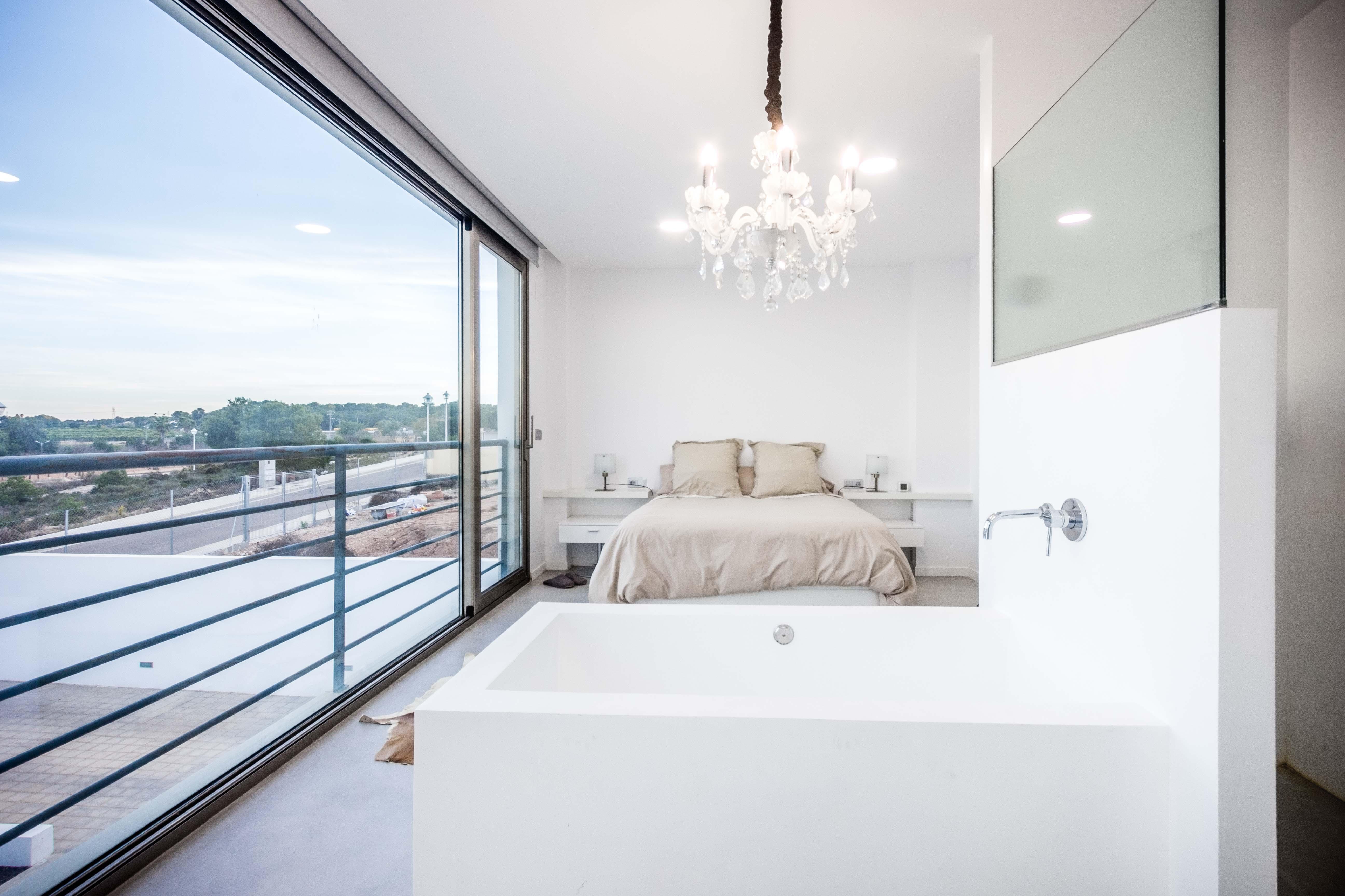 Bañera exenta de microcemento blanco en dormitorio en casa mediterranea. Chiralt arquitectos Valencia.