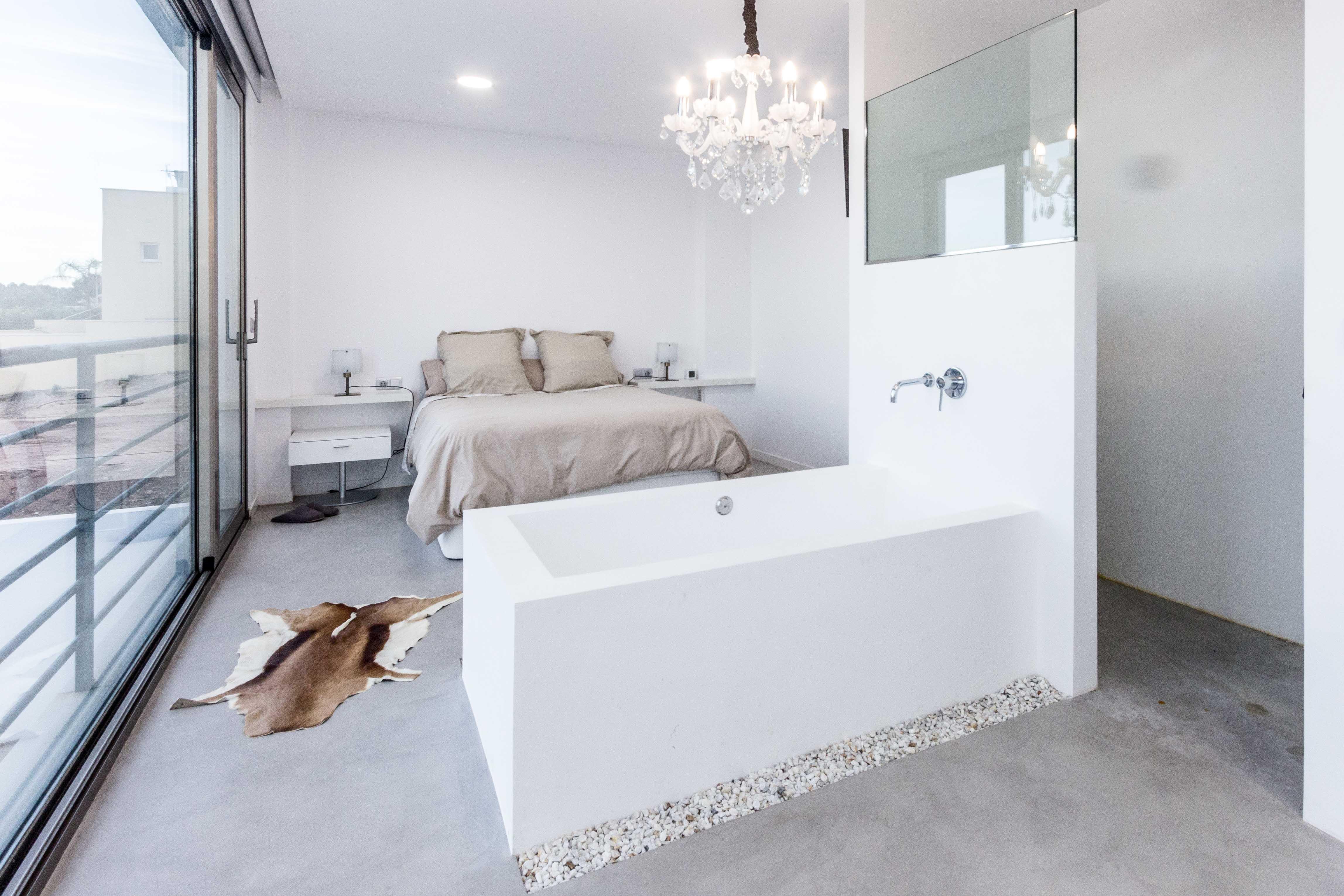 Bañera exenta en dormitorio de microcemento blanco en casa cubo mediterranea. Chiralt arquitectos Valencia.