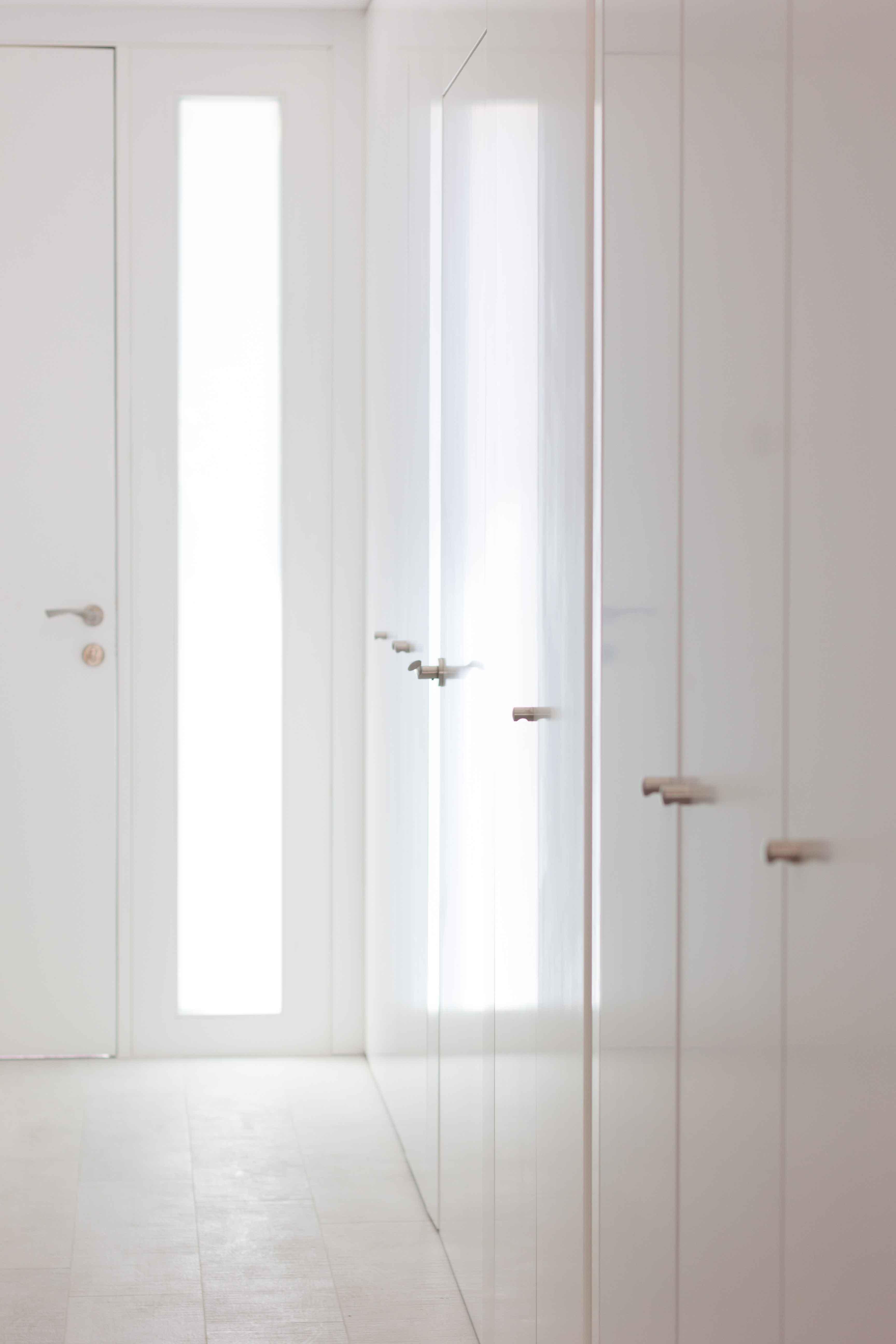 Recibidor con luz natural y armario blanco minimalista low cost en reforma de casa. Chiralt Arquitectos Valencia.