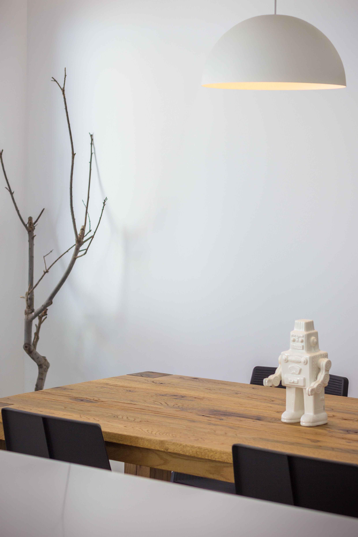 Lámpara de comedor blanca y redonda. Mesa de comedor de madera con sillas negras.Decoración de comedor estilo nórdico con mesa de madera y robot en reforma de casa. Chiralt Arquitectos Valencia.