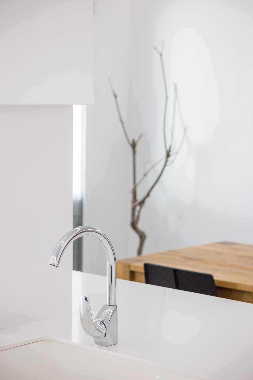 Grifo curvo en isla de cocina blanca. Reforma de vivienda de pueblo - Company- Chiralt Arquitectos Valencia