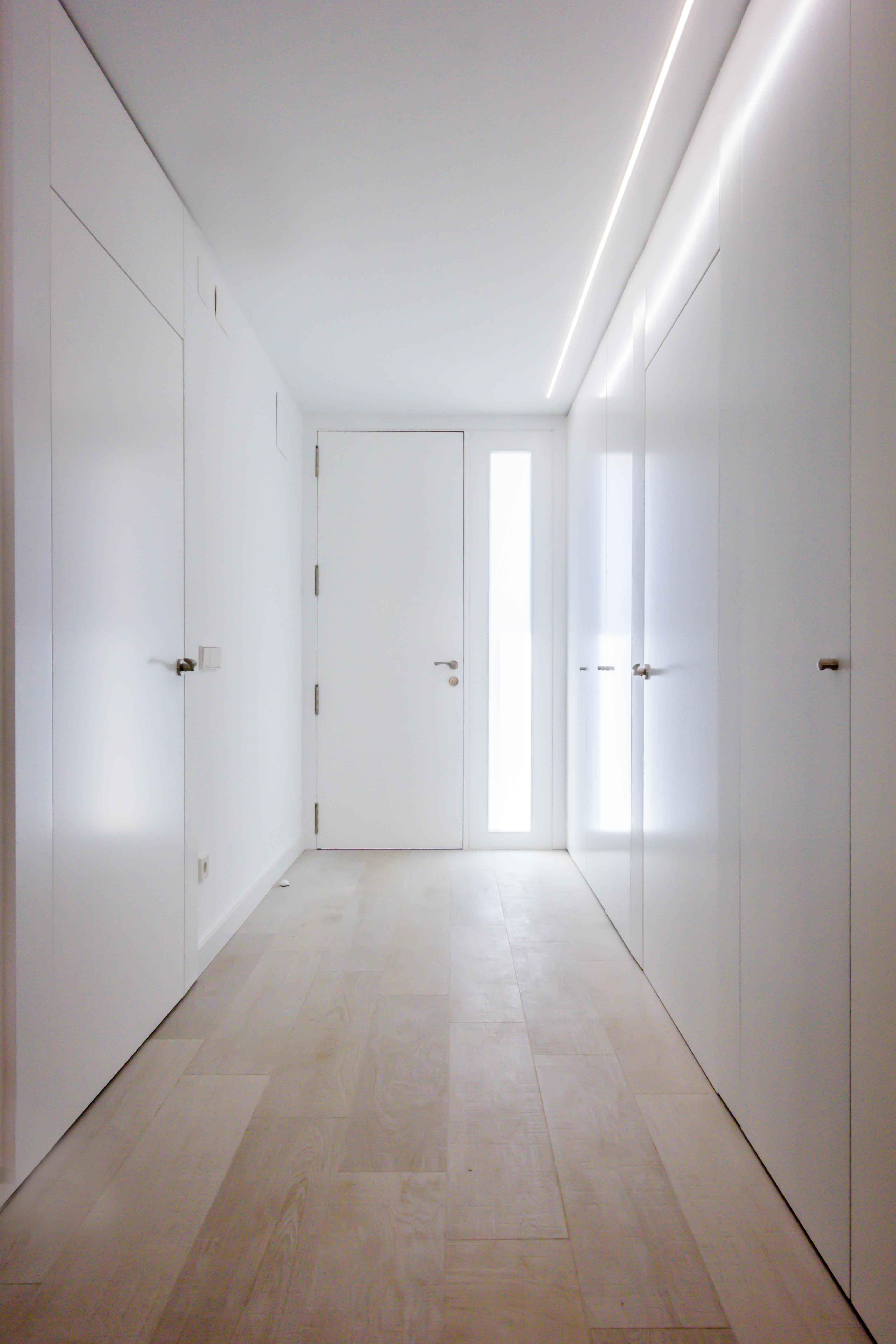 Recibidor con luz natural y armario blanco con puertas enrasadas minimalista low cost en reforma de casa. Chiralt Arquitectos Valencia.