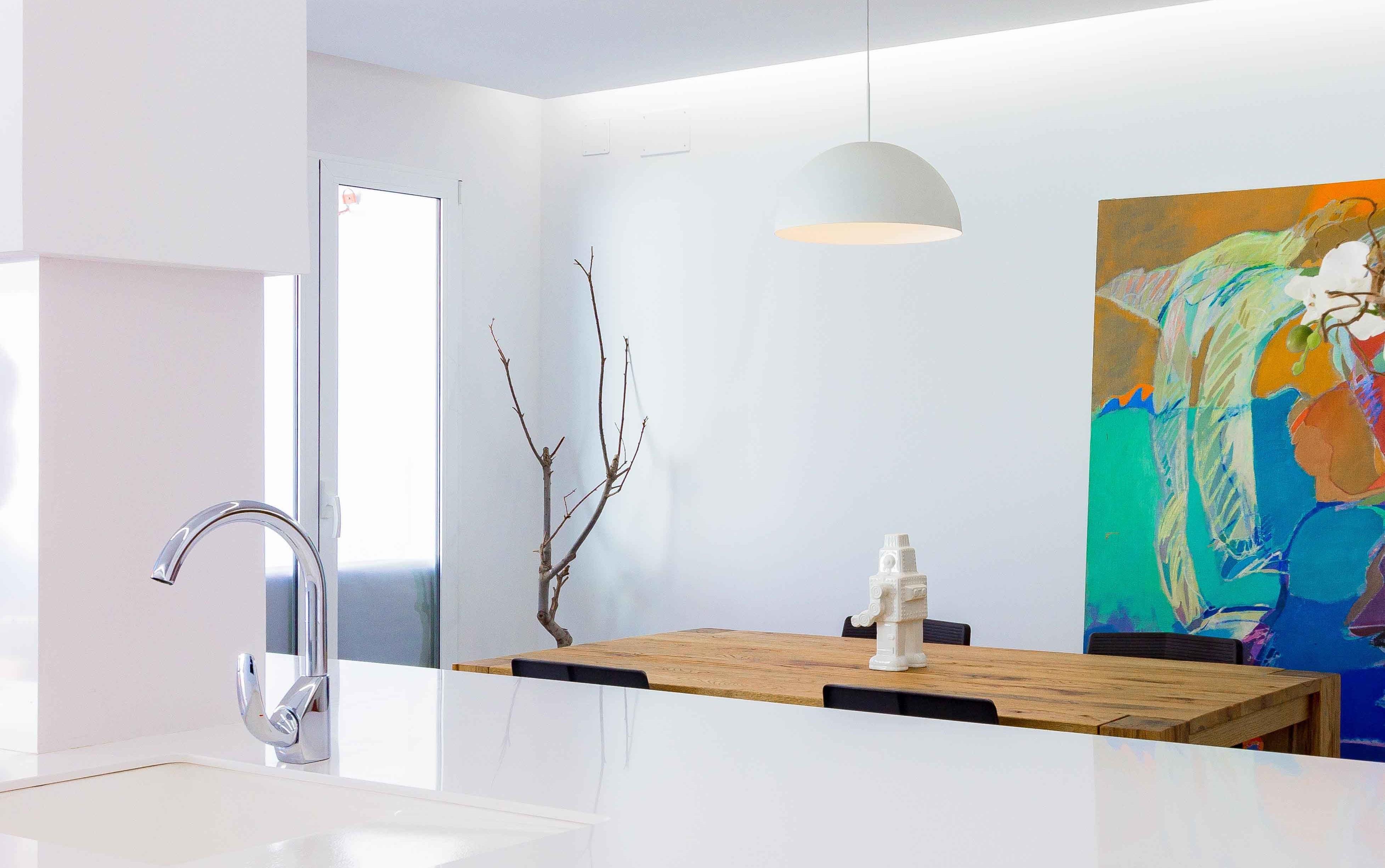 Decoración de cocina comedor estilo nórdico minimalista con mesa de madera maciza en reforma de casa. Lámpara de cocina blanca y encimera blanca de granito.Chiralt Arquitectos Valencia.