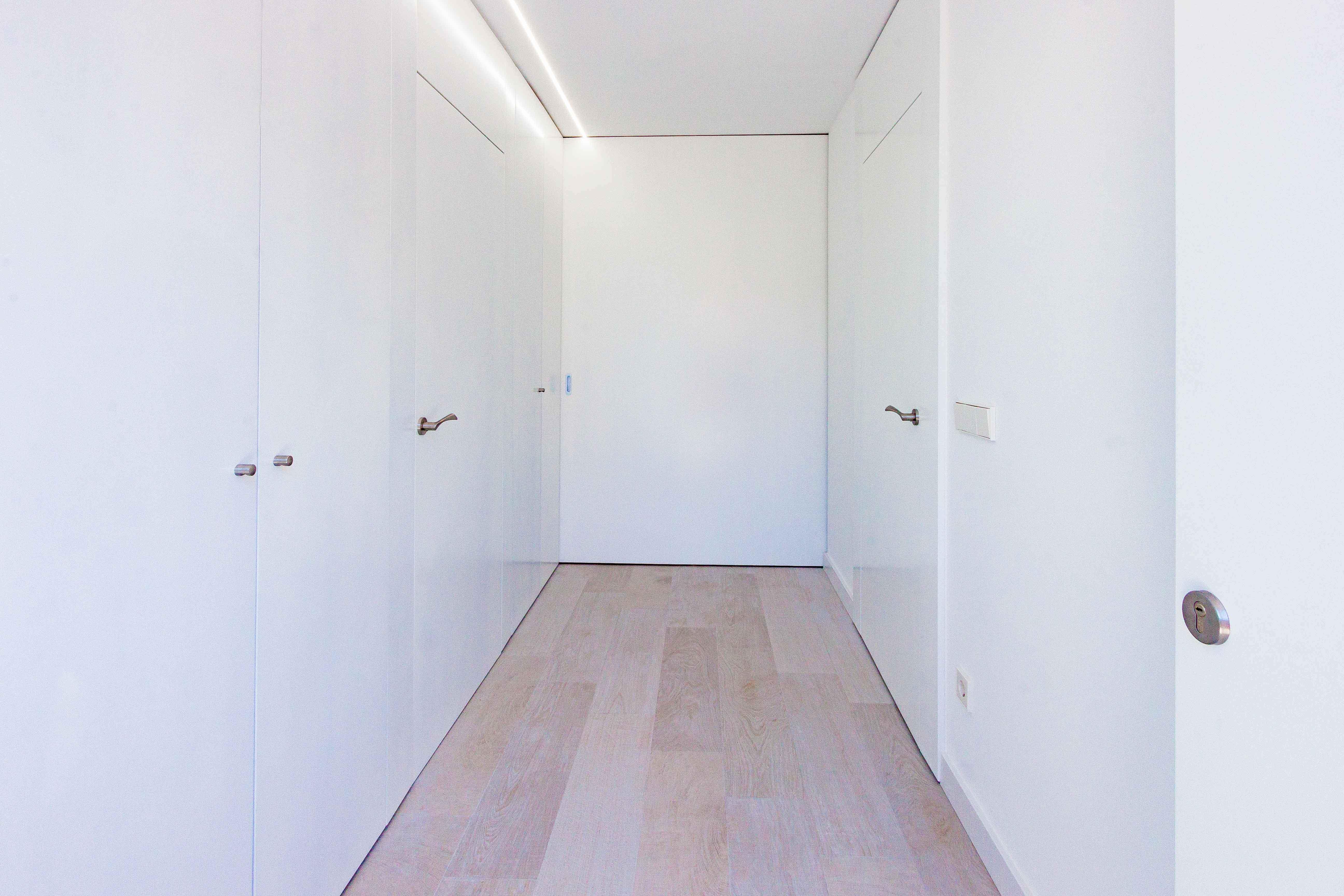 Armario blanco empotrado con puertas enrasadas en hall de reforma de casa. Chiralt Arquitectos Valencia.