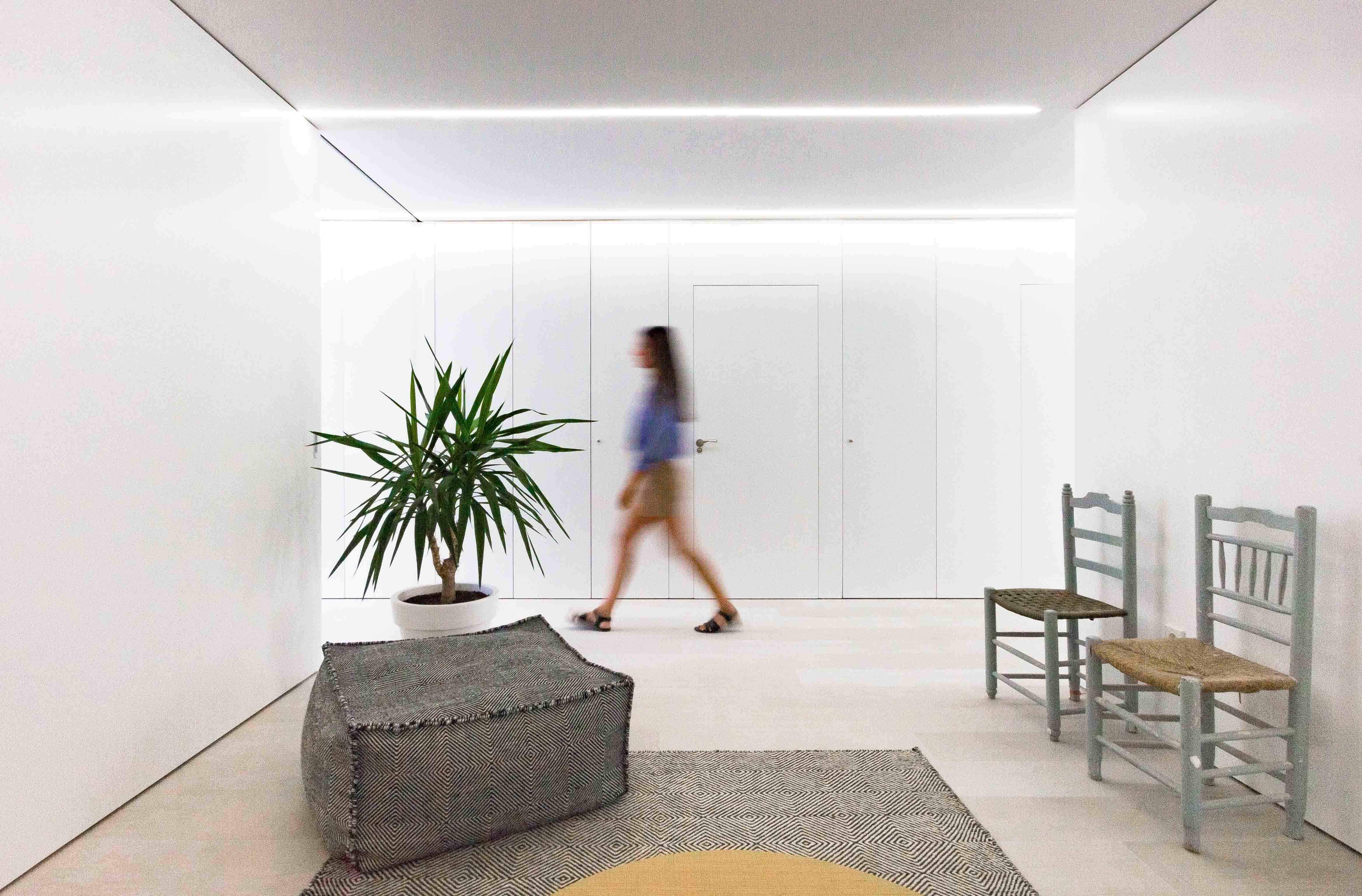 Puf y alfombra negfra y blanca con sillas rusticas y plantas decorando el salon minimal. Puertas blancas integradas.
