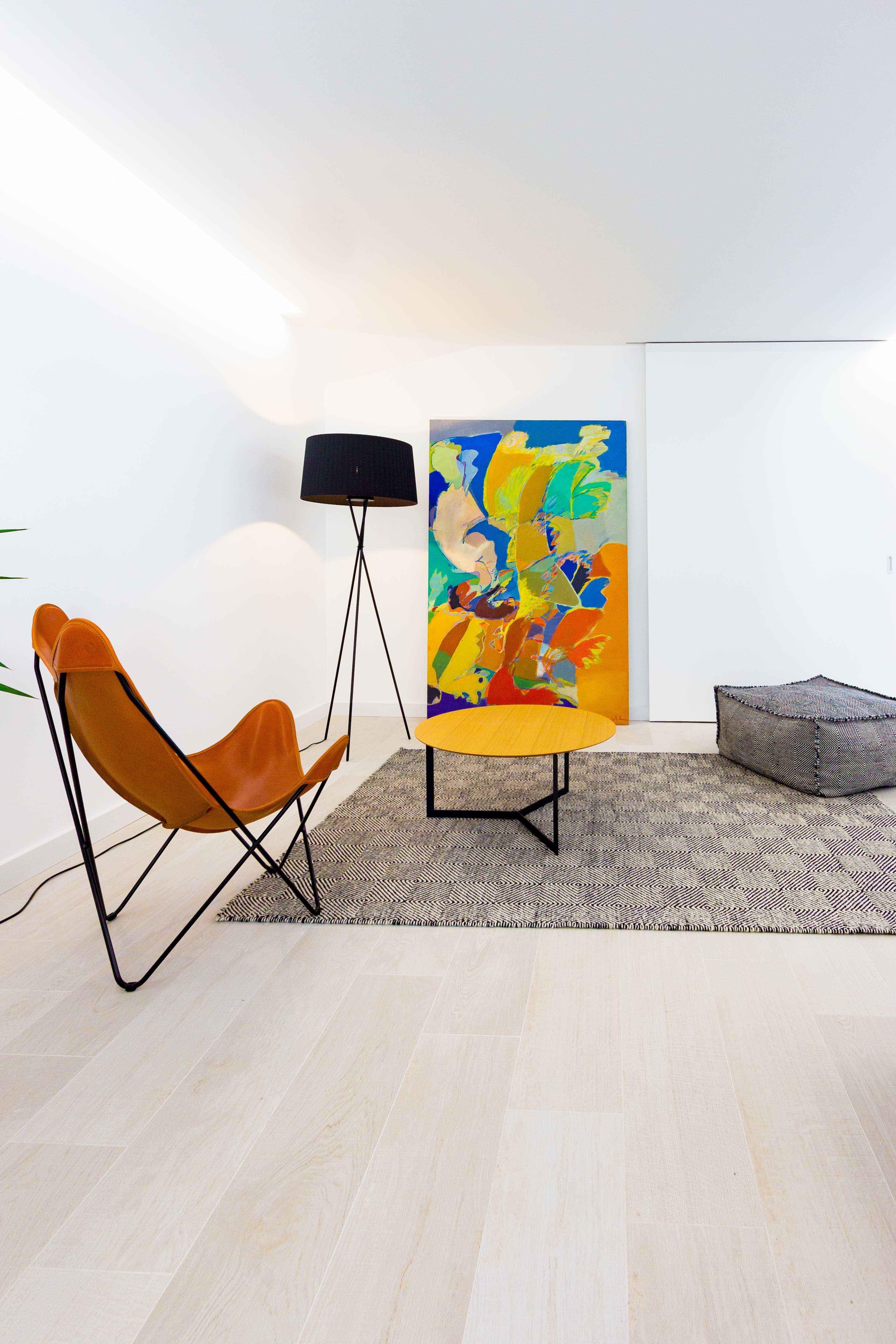 Lampara de pie negra en salon moderno y minimalista. Sillon de cuero con alfombra negra y blanca y puf. Cuadro de gran tamaño abstracto