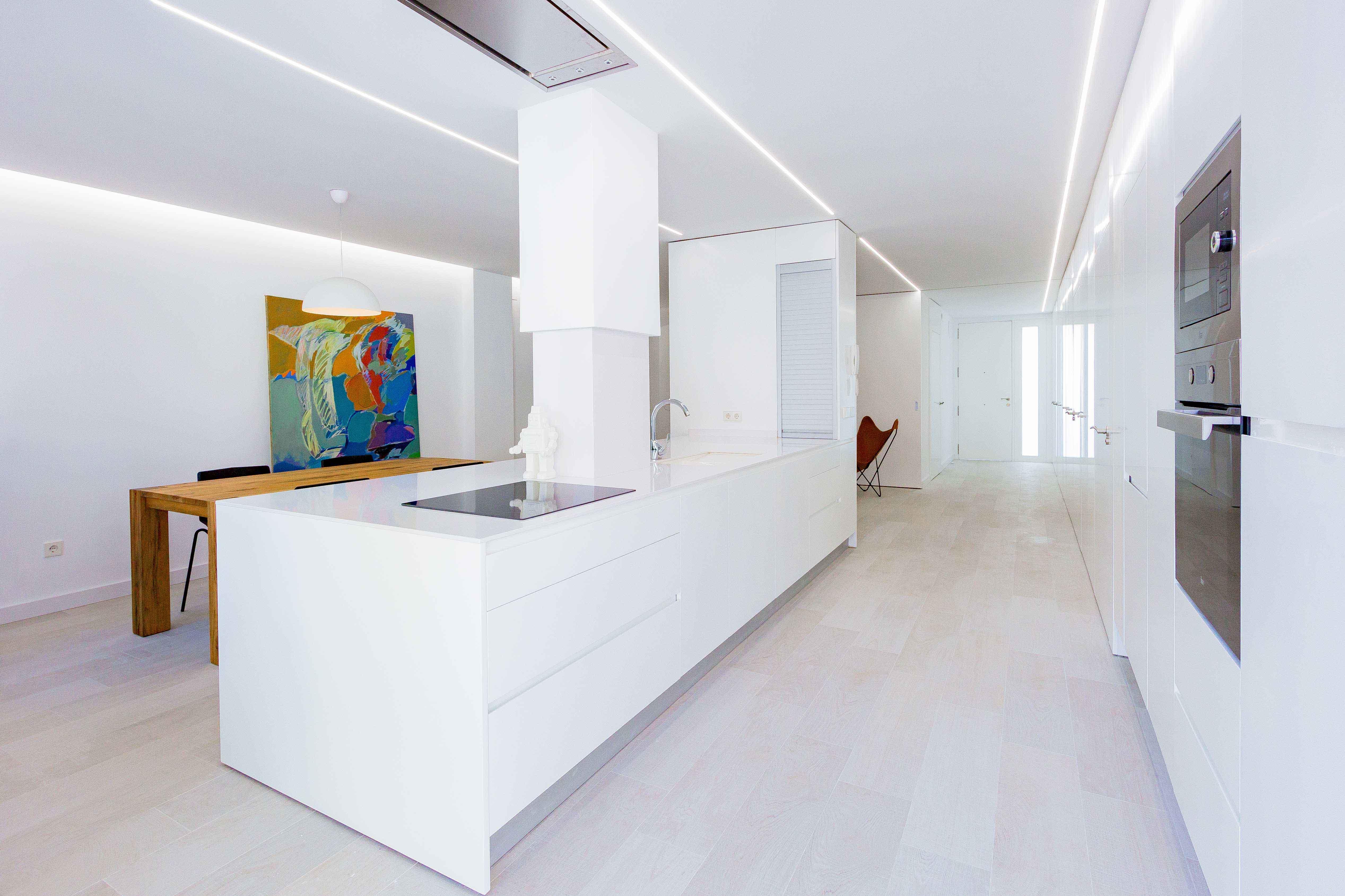 Isla con encimera y armario blancos en cocina abierta al salón y la terraza. Mesa de comedor de madera rustica. Horno y microondas integrados.