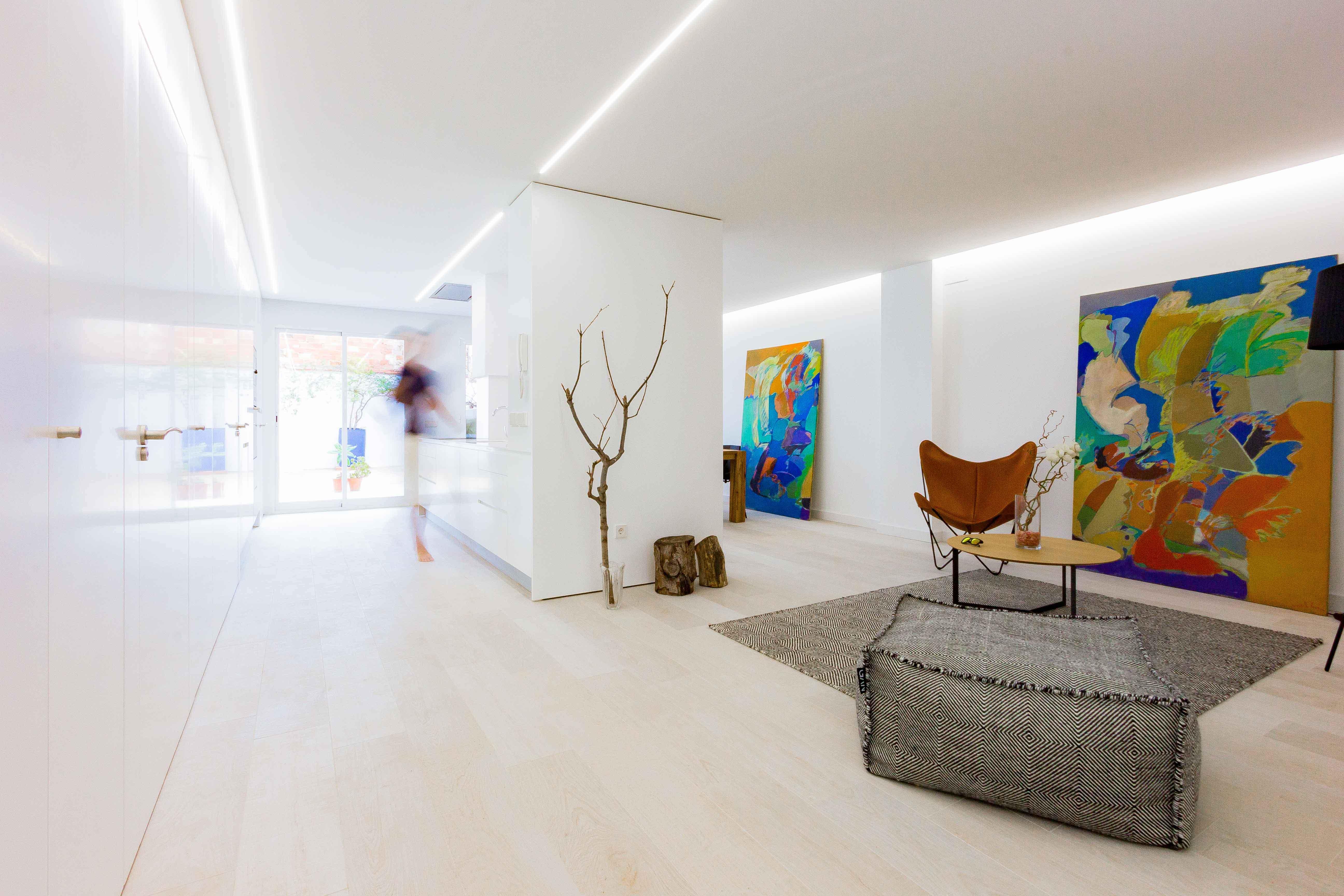 luminoso Salón comedor cocina minimalista en reforma de casa low cost. Chiralt Arquitectos Valencia.