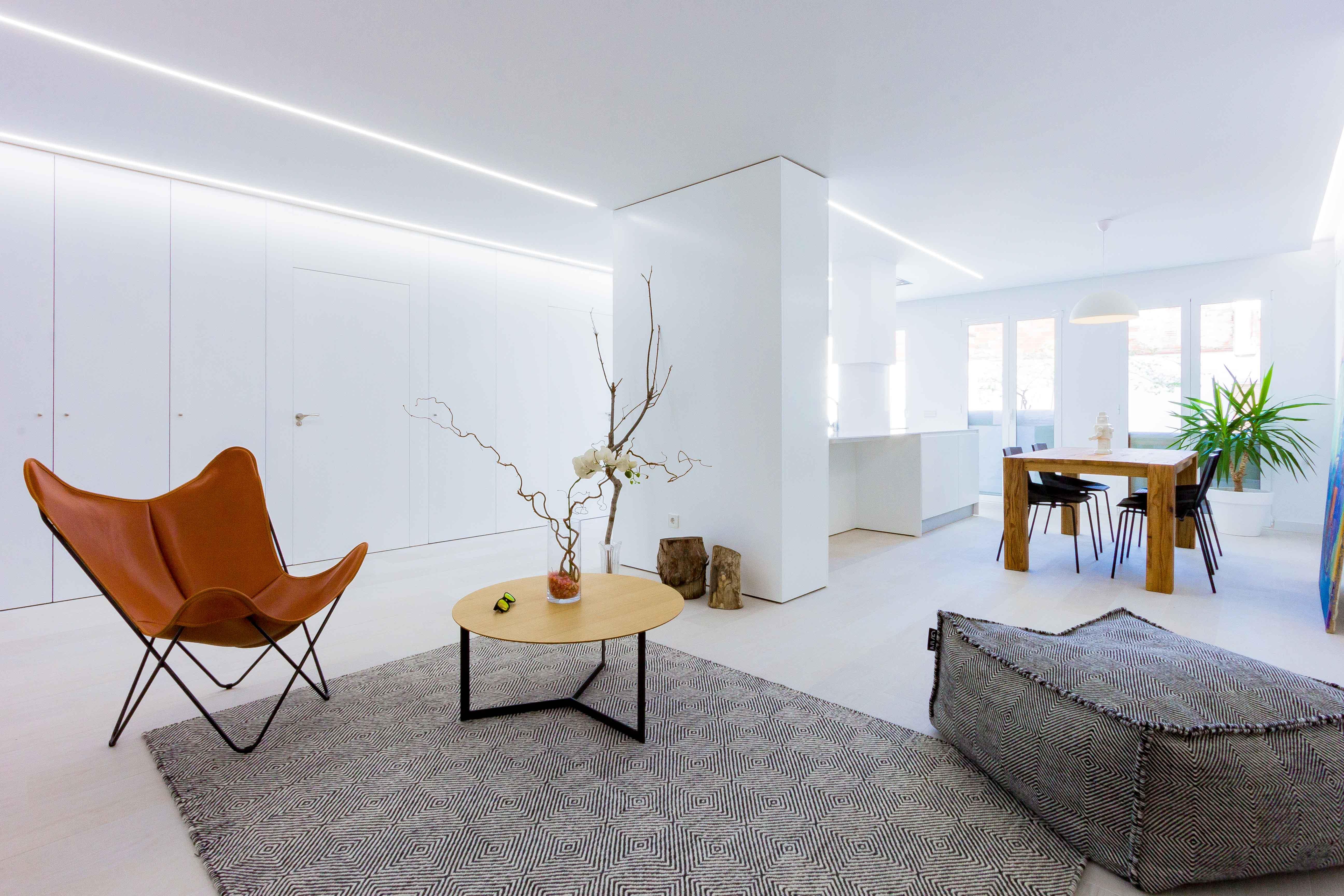 Salón comedor con cocina blanca abierta, moderna y minimalista. Mesa de comedor de madera con sillas negras. Puf y sillon de cuero