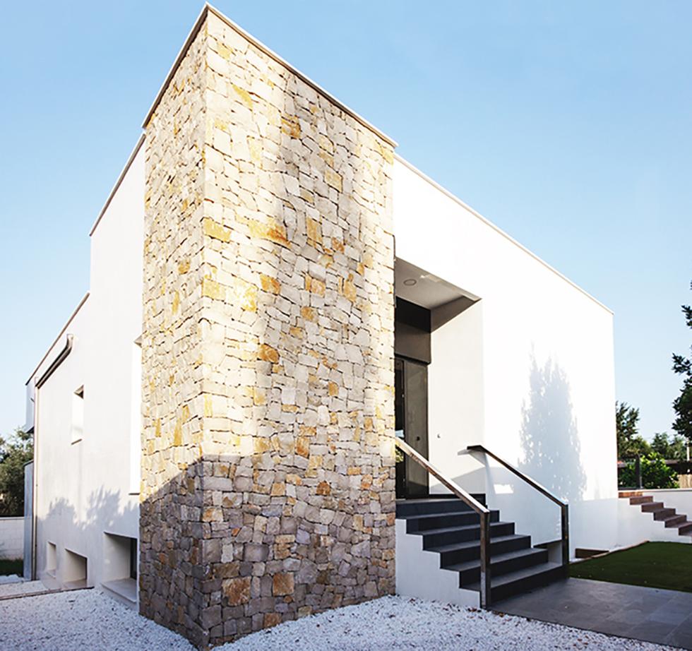 Entrada de casa moderna con pared de piedra y escaleras con barandilla de acero