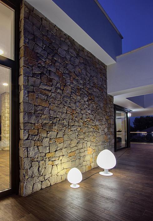 Foto de noche de pared de piedra en casa moderna con suelo de madera