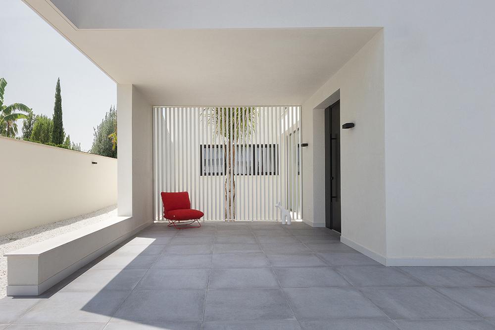 Entrada de chalet moderna y minimalista en blanco y con vistas a un patio interior