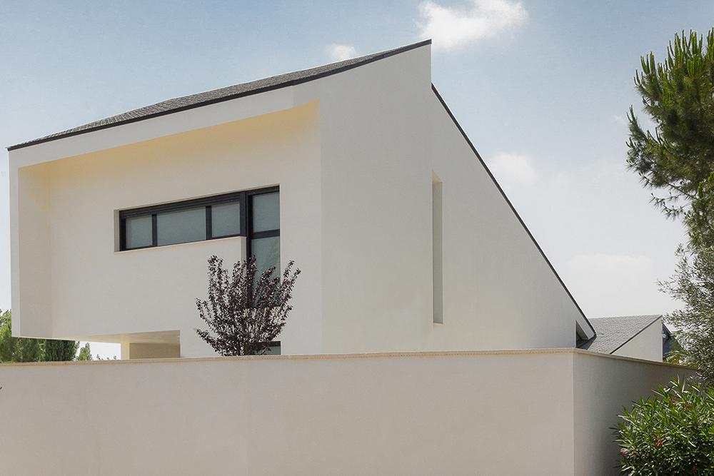 Casa blanca, moderna y minimalista con cubierta de tejas negras inclinadas