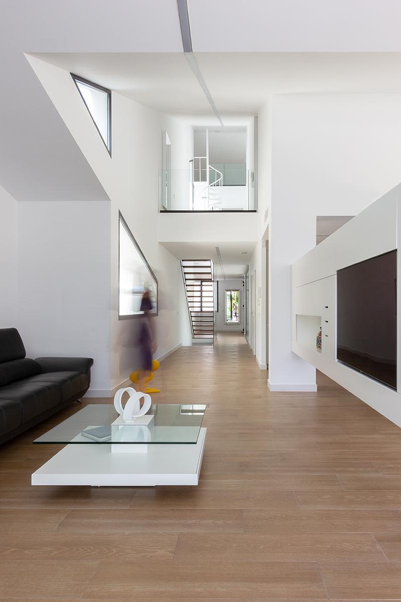 Mesa de centro de cristal y blanco. Salon con doble altura. Ventanas triangulares negras