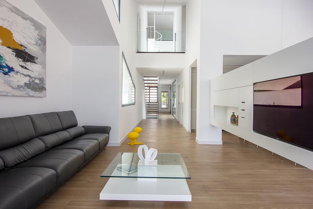 Salon de doble altura. Minimalista y moderno. Suelo porcelanico imitacion madera.