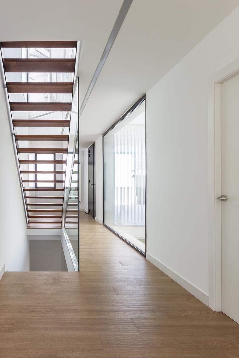 Escalera de madera y acero negro en pasillo con luz natural por gran ventanal negro que da a patio interior