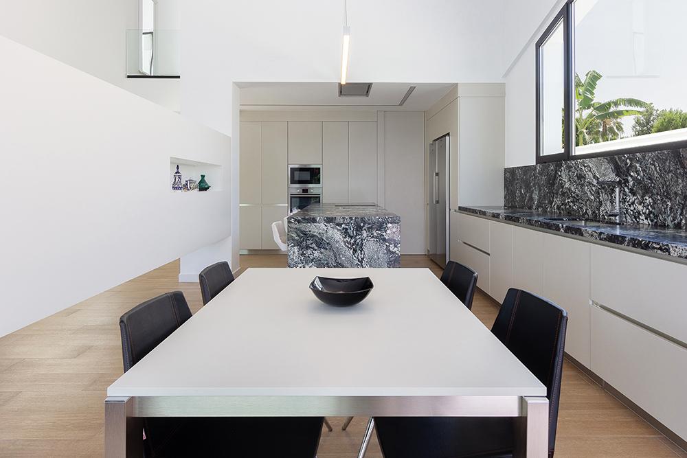 Cocina blanca con isla de marmol negro y mesa de comedor blanca