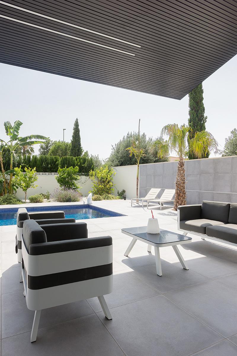 Terraza de chalet con piscina y sillones de exterior en gris y blanco