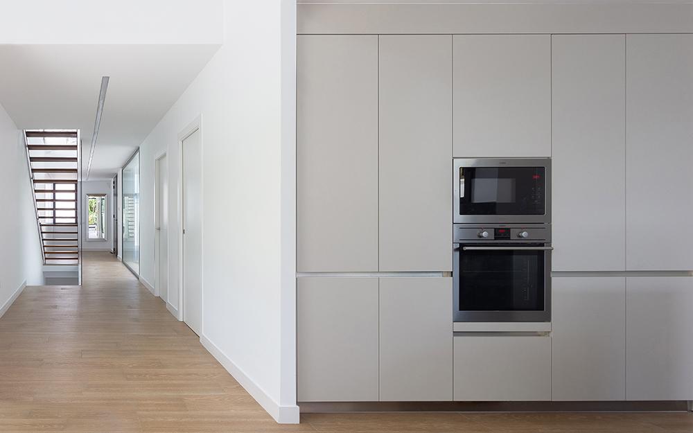 Cocina abierta en blanco con horno y microondas. Pasillo ancho con suleo de porcelanico imitacion madera. Escalera metalica y madera abierta