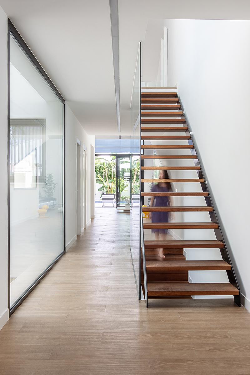 Escaler moderna de madera y acero negra con peldaños abiertos. Grandes ventanales negros abiertos al exterior