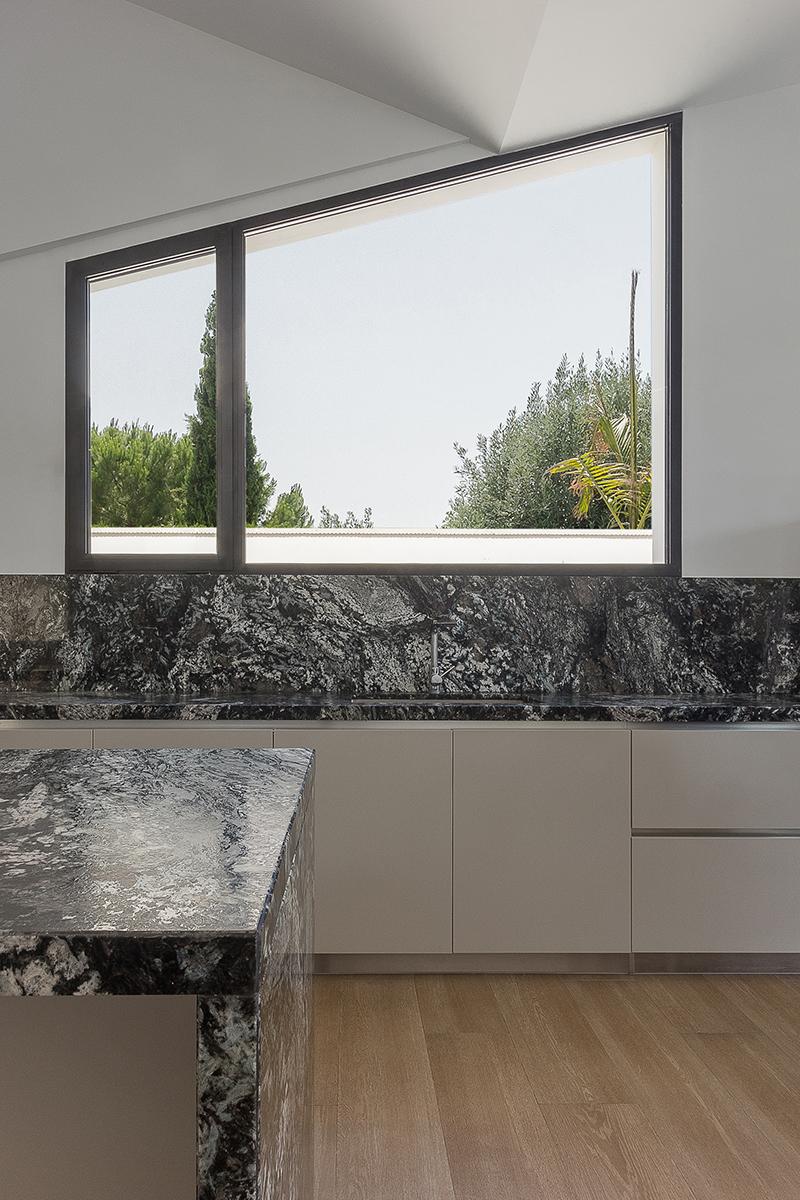 Ventana inclinada en cocina con encimeras de marmol negro