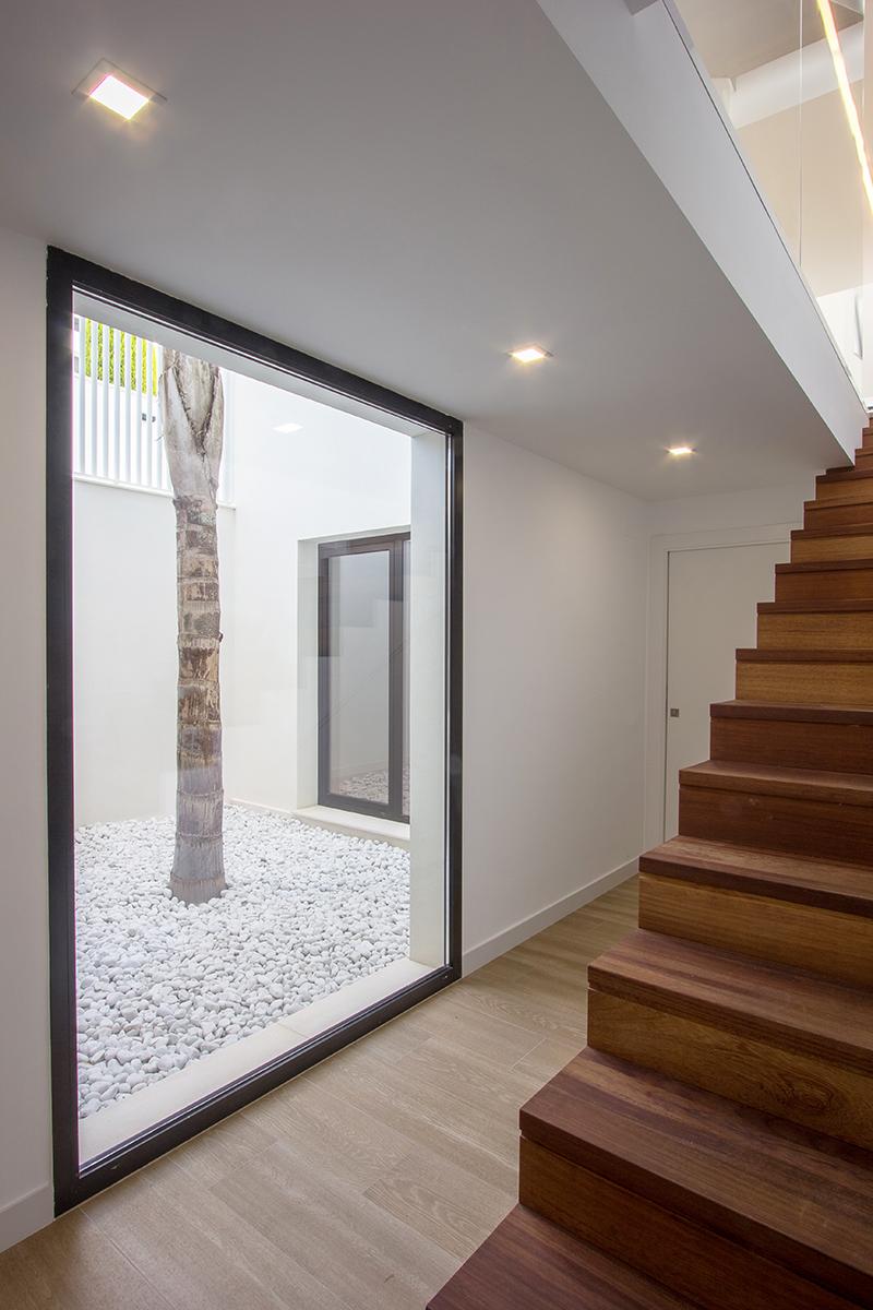 Escalera de madera en patio interior de piedras blancas con arbol