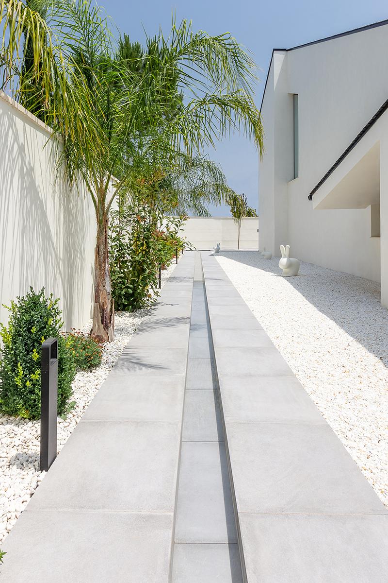 Casa moderna y minimalista con tejado negro inclinado y jardin de piedras con fuente alargada estilo arabe