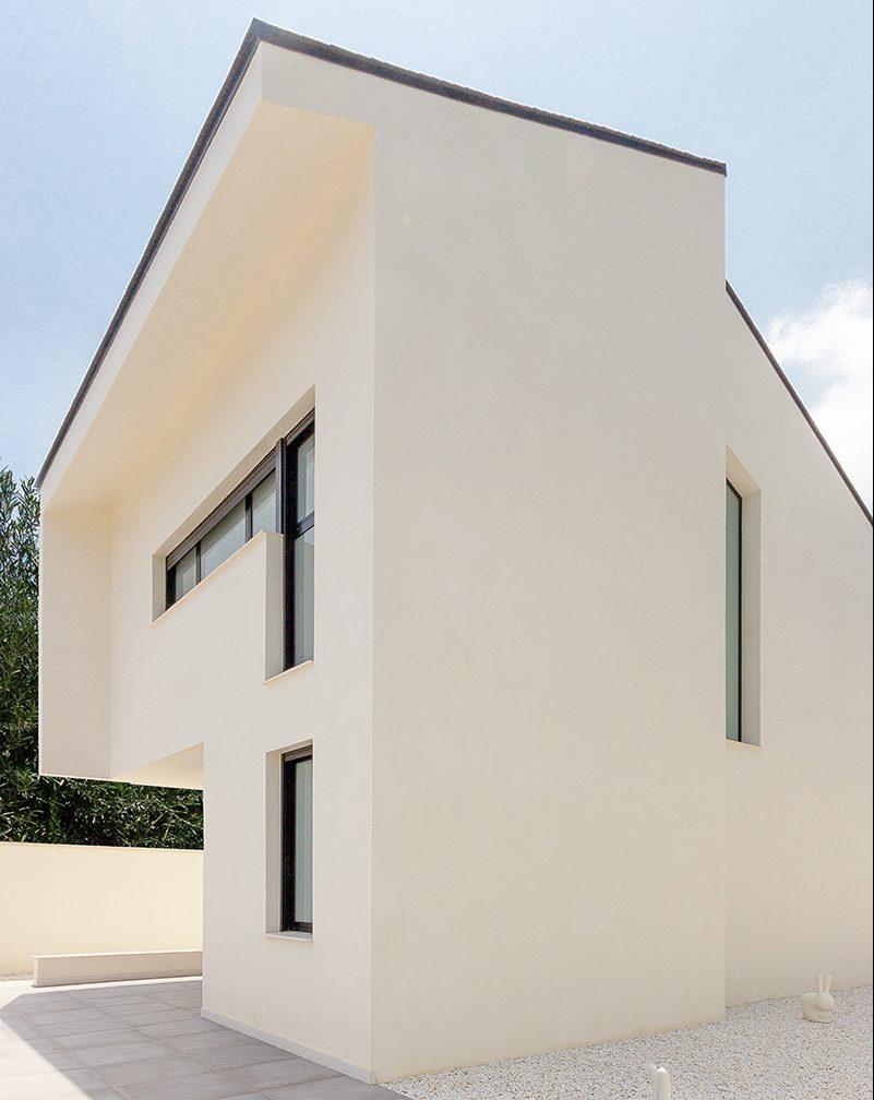 Casa blanca, moderna y minimalista con cubiertas negras inclinadas