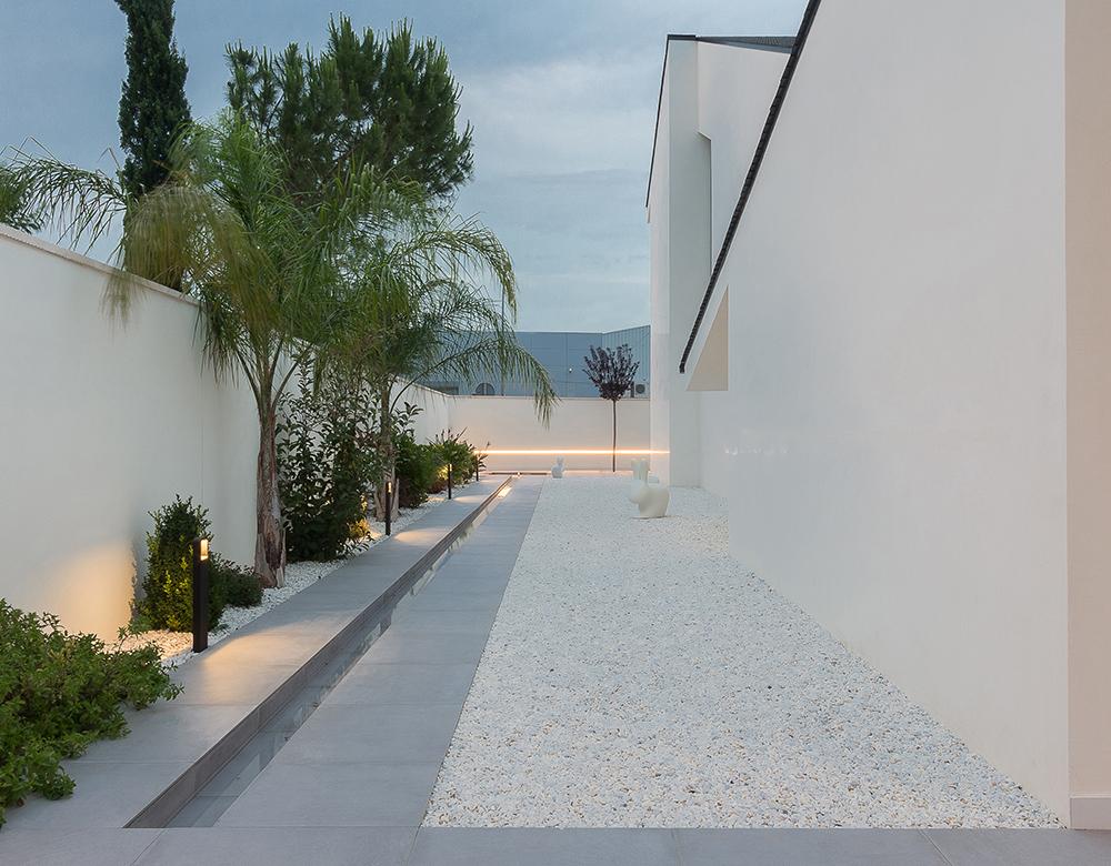 Jardin con grava blanca. Fuente estilo arabe.Casa blanca, moderna y minimalista con cubierta de tejas negras inclinadas