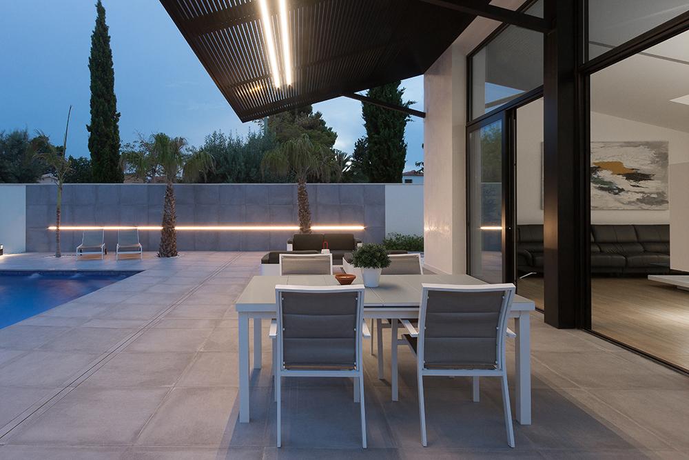 Terraza chalet con piscina. Salon con vistas al exterior y grandes ventanales negros