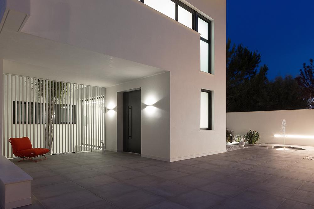 Entrada puerta principal iluminada. Patio interior con palmera. Fuente en la entrada