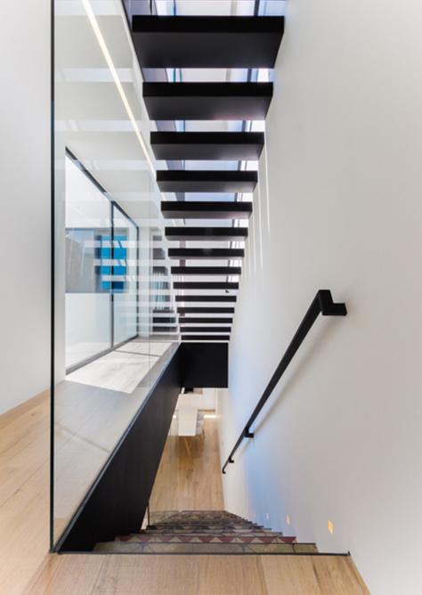 Escalera minimalista de acero negro industrial. Barandilla de cristal de casa de pueblo moderna de Chiralt Arquitectos Valencia