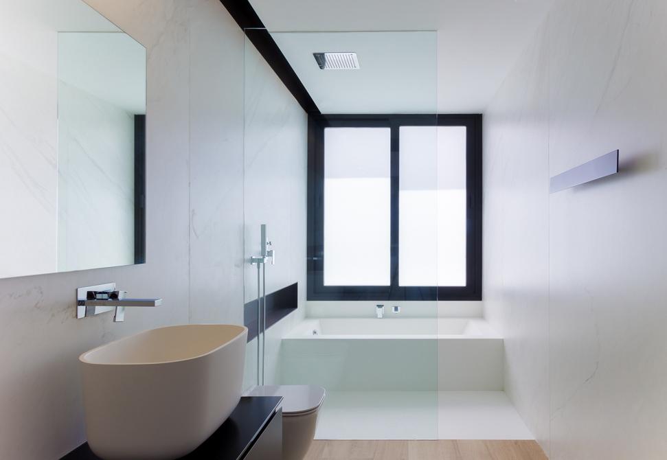 Baño de marmol blanco minimalista con lavabo en sobre encimera negra en casa de pueblo moderna Chiralt Arquitectos Valencia