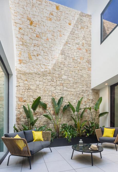 Patio interior con muro de piedra natural de casa de pueblo moderna de Chiralt Arquitectos Valencia
