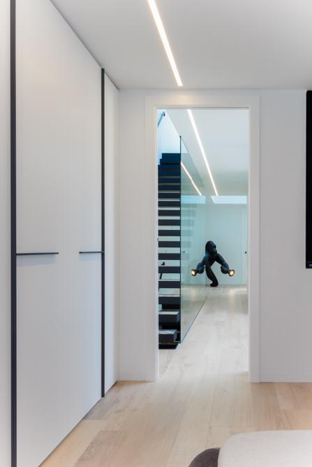 Casa minimalista blanca. Suelo de madera. Escalera volada de acero negro con barandilla cristal.Pasillo moderno en casa de pueblo moderna de Chiralt Arquitectos Valencia