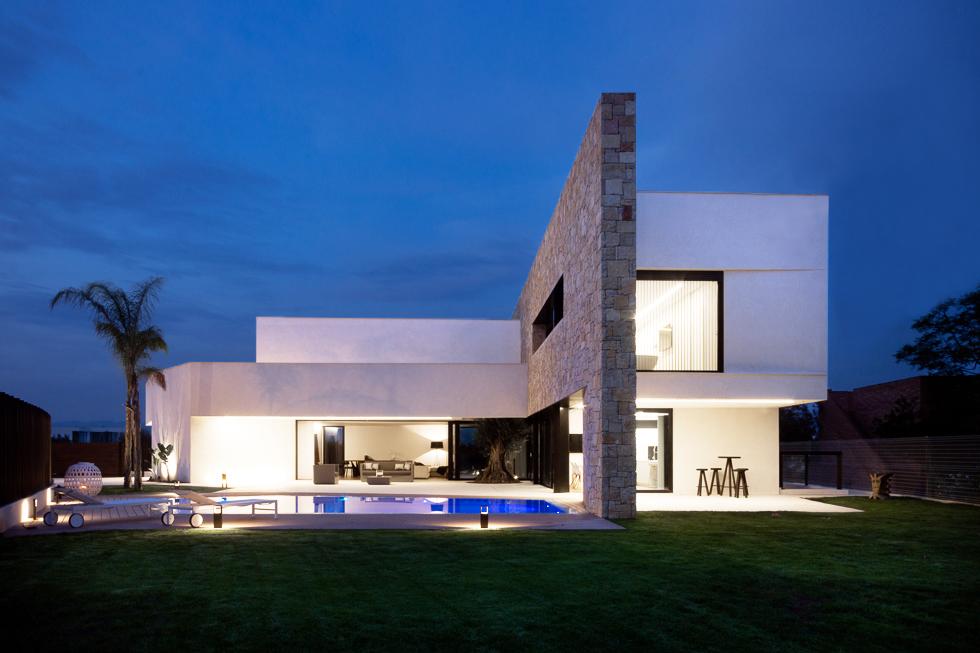 Casa de lujo con pared de piedra y piscina