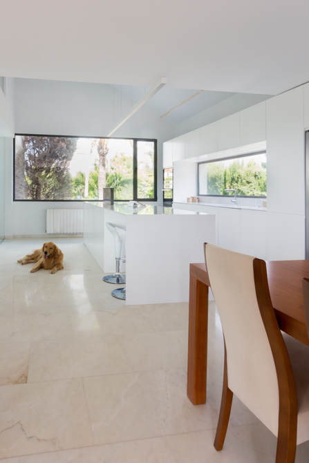 Cocina moderna blanca con isla con ventana en vivienda mediterránea. Chiralt Arquitectos Valencia