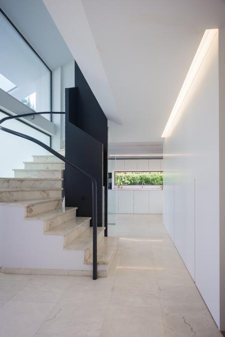 Pasillo con escalera moderna y suelo de marmol en vivienda mediterranea. Chiralt Arquitectos Valencia