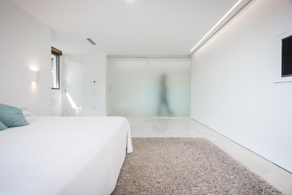 Dormitorio minimalista con pared de cristal en reforma integral. Chiralt Arquitectos Valencia
