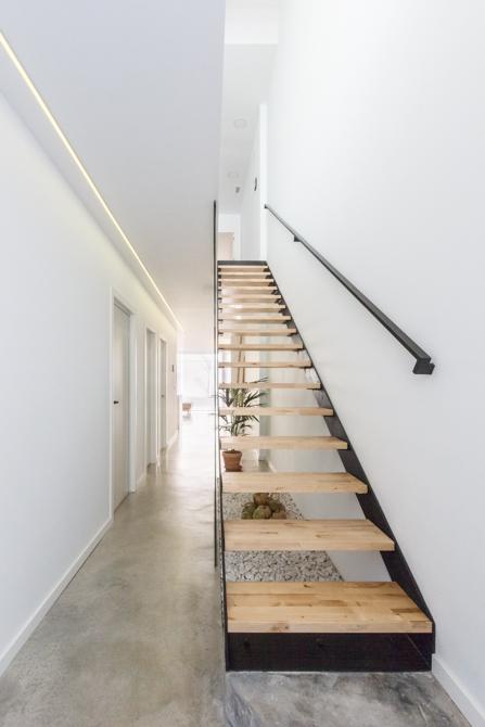 Escalera escandinava de madera y hierro en vivienda estilo nórdico.Suelo de microcemento gris
