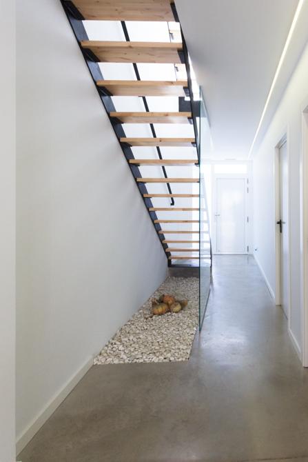 Escalera estilo nórdico de hierro y cristal en vivienda estilo nórdico. Suelo gris de hormigón pulido
