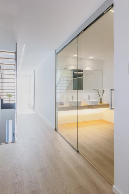 Baño moderno abierto con puerta de cristal, lavabo doble sobre encimera de maderay suelo de madera en vivienda estilo nórdico - Chiralt Arquitectos Valencia