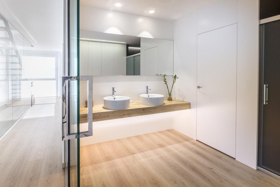 Baño moderno abierto con puerta de cristal y suelo de madera en vivienda estilo nórdico - Chiralt Arquitectos Valencia