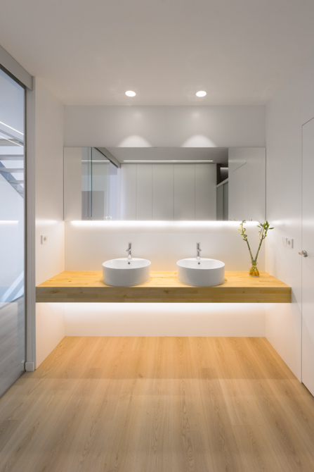 Baño escandinavo con dos lavabos sobre encimera de madera y suelo parquet en vivienda estilo nórdico - Chiralt Arquitectos Valencia