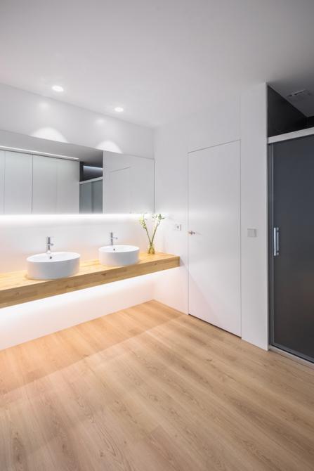 Baño moderno con dos lavabos sobre encimera de madera y suelo parquet en vivienda estilo nórdico - Chiralt Arquitectos Valencia