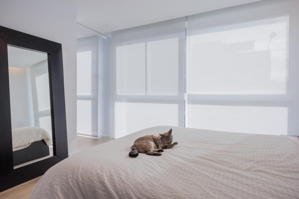 Dormitorio moderno en blanco con cama y gato en vivienda estilo nórdico - Chiralt Arquitectos Valencia