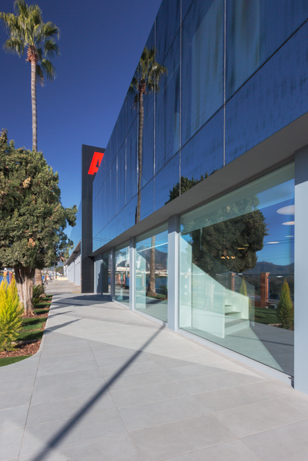 Fachada de cristal negra y transparente de oficinas con jardin de cesped y palmeras
