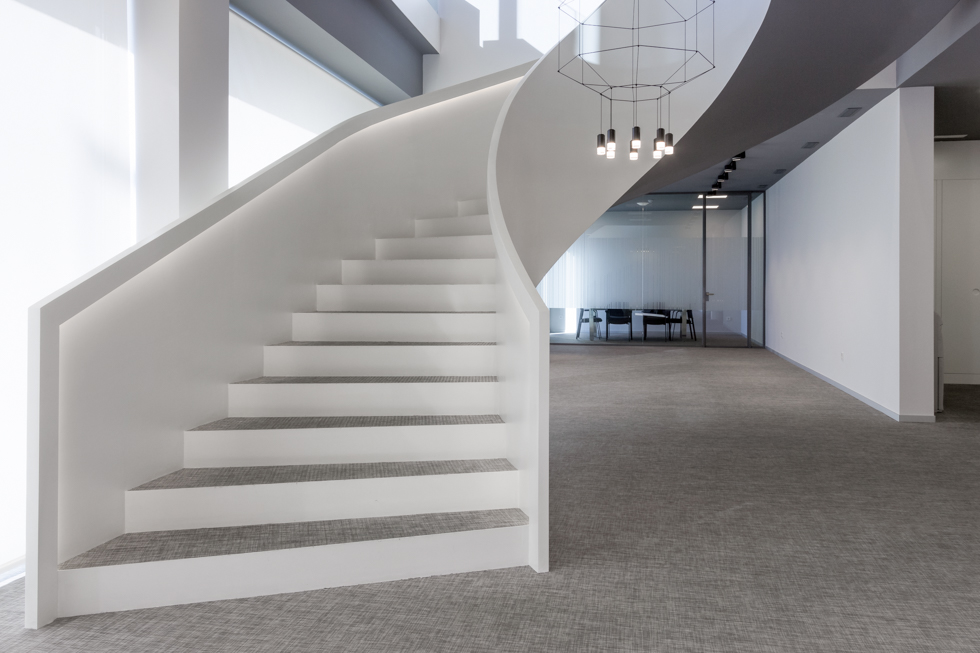 Escalera blanca y minimalista en espiral en hall de oficinas modernas con lampara moderna de vibia