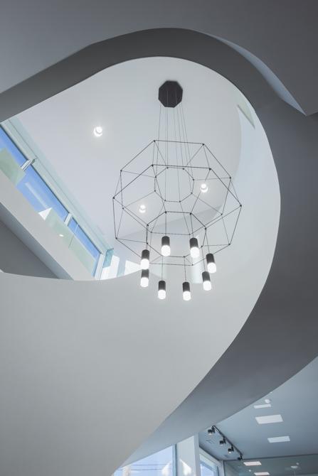 Escalera blanca en espiral en hall de oficinas modernas con lampara moderna de vibia